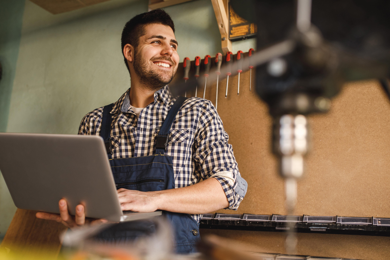 Tischler steht mit einem Laptop in seiner Werkstatt und lächelt.